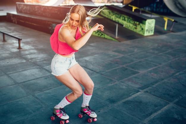Bella ragazza bionda sta facendo alcuni trucchi durante i rollerblade