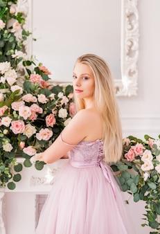 Bella ragazza bionda in un abito viola morbido lungo di fiori in posa. concetto di profumi, moda e bellezza