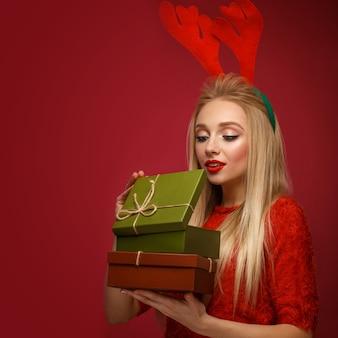 Bella ragazza bionda nell'immagine di un nuovo anno con scatole di regali in mano e corna di cervo sulla testa. fronte di bellezza con trucco festivo. foto scattata in studio.