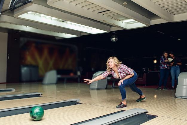 Bella ragazza bionda gioca a bowling nel club