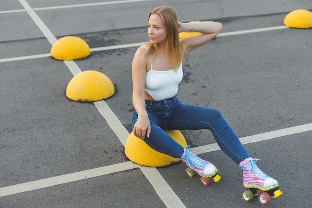 Bella ragazza bionda in rulli che si siede nello skate park