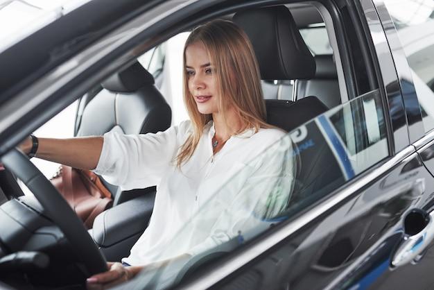 Bella ragazza bionda che si siede nella nuova automobile con interni neri moderni
