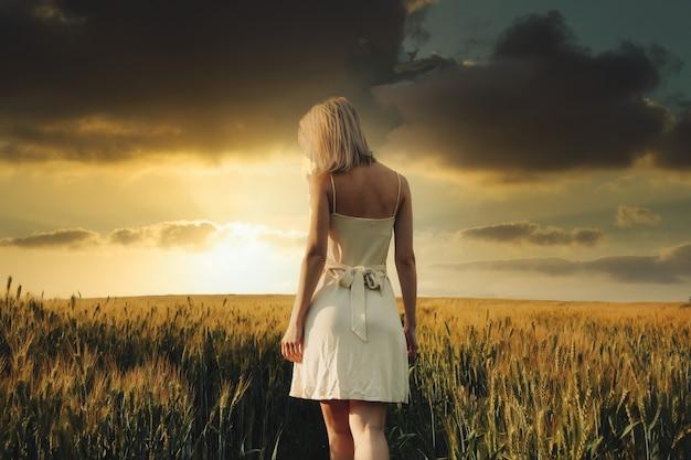 Bella ragazza bionda nel campo di grano nel tempo del tramonto