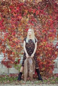 Bella ragazza bionda con il ritratto dell'uva dei fogli di autunno