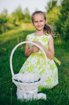Bella ragazza bionda con coniglietti seduto sull'erba verde. conigli festivi. coniglietto di pasqua