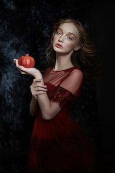 Bella ragazza bionda con frutta melograno nelle sue mani. ritratto della primavera di una ragazza in un vestito rosso che rompe un melograno, succo che scorre giù le sue mani