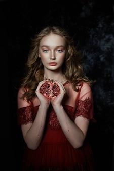 Bella ragazza bionda con frutta di melograno nelle sue mani. ritratto primaverile di una ragazza con un vestito rosso che rompe un melograno, il succo che scorre lungo le sue mani