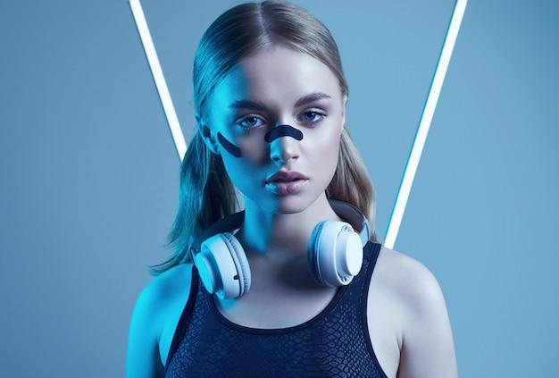 Bella ragazza bionda con musica d'ascolto delle cuffie bianche alle luci al neon
