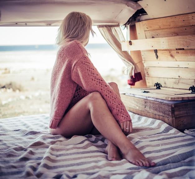 Bellissima modella bionda caucasica con un bel corpo e una posa sexy seduta all'interno di un vecchio camper vintage e guarda fuori verso l'oceano e la natura. parcheggiata in spiaggia per una vacanza alternativa gratuita