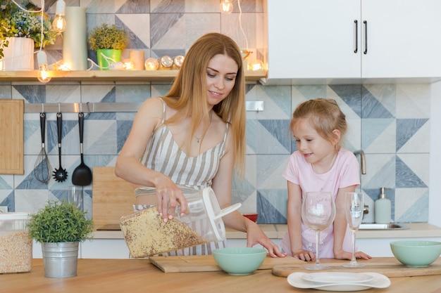 Bella madre bionda e piccola figlia carina divertendosi e giocando in appartamento alla moda con un design elegante