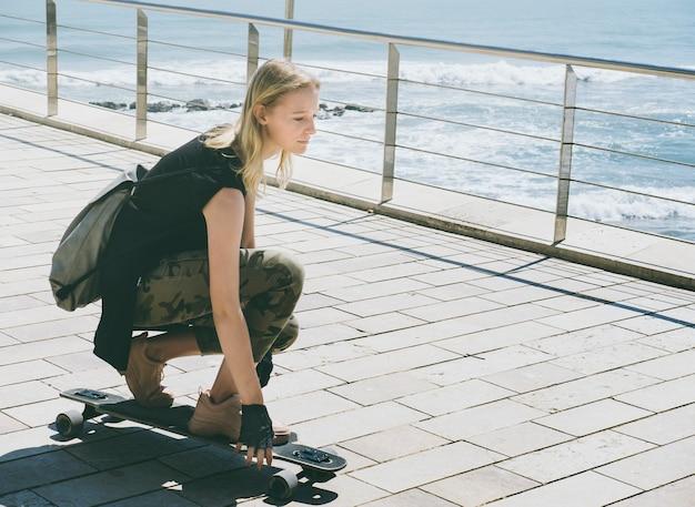 Bella bionda su uno skateboard in una calda giornata estiva in riva al mare