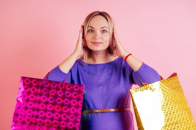 Bella faccina bionda donna incinta grande pancione che tiene le borse della spesa in studio su uno sfondo rosa. concetto di vendita e sconti