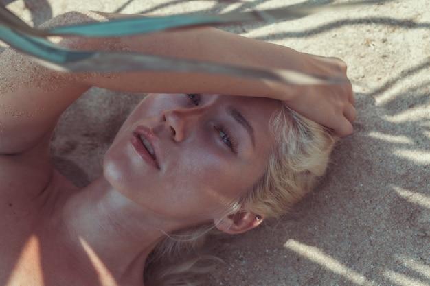 Bella ragazza bionda turistica sdraiata sulla spiaggia a pattaya