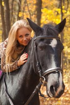 Bella bionda per una passeggiata a cavallo nel bosco autunnale