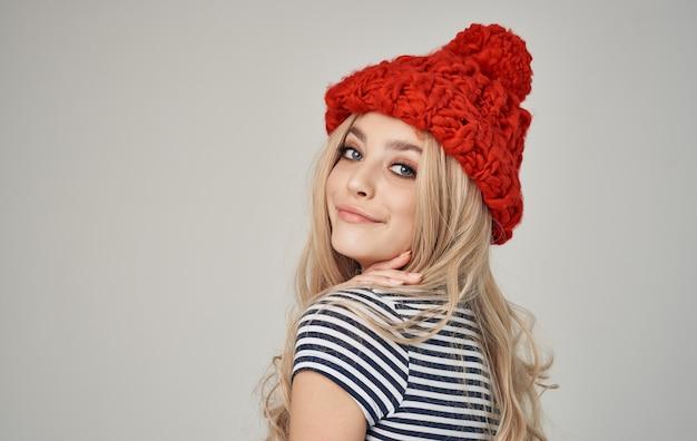 Bella bionda con un cappello caldo e una maglietta a righe su uno sfondo chiaro