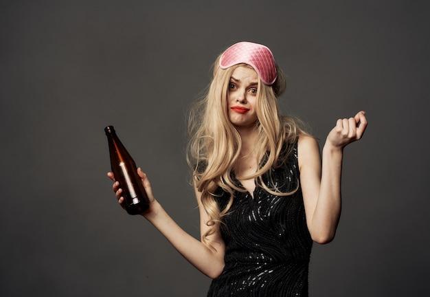 Bella bionda con una bottiglia di birra in mano e una maschera rosa in testa