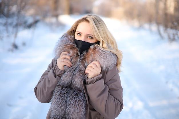 Bella bionda con un collo di pelliccia in una maschera protettiva nera in inverno nel parco