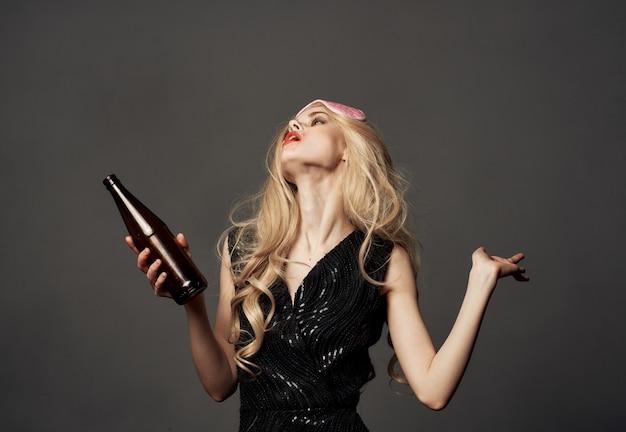 Bella bionda con una maschera per dormire rosa e una bottiglia di birra