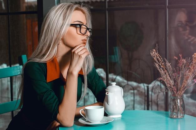 Bella donna bionda nella caffetteria pensando a qualcosa e guardando la finestra. bella ragazza in caffè che guarda lontano.