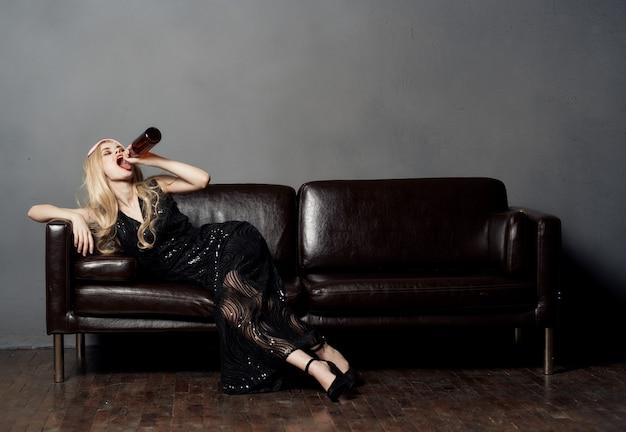 Bella donna bionda sul divano con una bottiglia di birra e in un vestito nero. foto di alta qualità