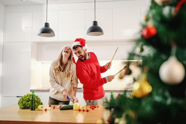 Il bello cetriolo biondo di taglio della donna mentre sta e l'uomo sta fingendo di suonare la batteria con i cucchiai di miscelazione