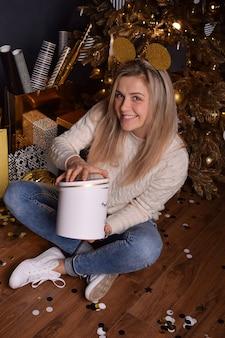 Bella donna bionda che tiene una scatola con un regalo di natale nelle sue mani e sorride felicemente