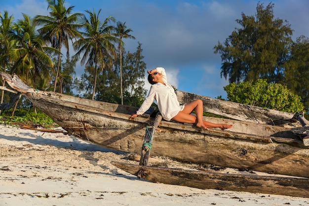 Bella donna bionda nel costume da bagno bianco lavorato a maglia che si siede sulla spiaggia solitaria con acqua turchese e sabbia bianca vicino al dhow tradizionale del peschereccio. zanzibar. nungwi.