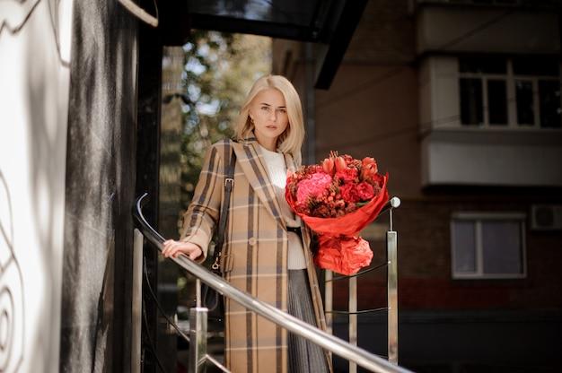 Bella donna bionda in cappotto scozzese con un grande mazzo di fiori rosso