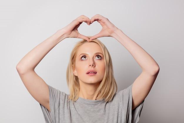 Bello gesto biondo di amore di manifestazione della donna sulla parete bianca