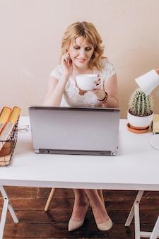 Una bella donna bionda si siede e lavora al laptop e beve caffè o tè