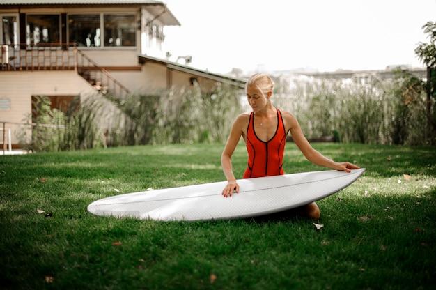 Bella donna bionda che si siede sul prato inglese verde con un wakeboard