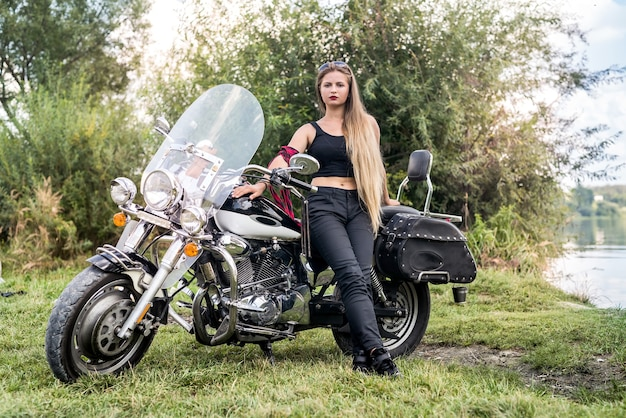Una bella donna bionda seduta su una moto