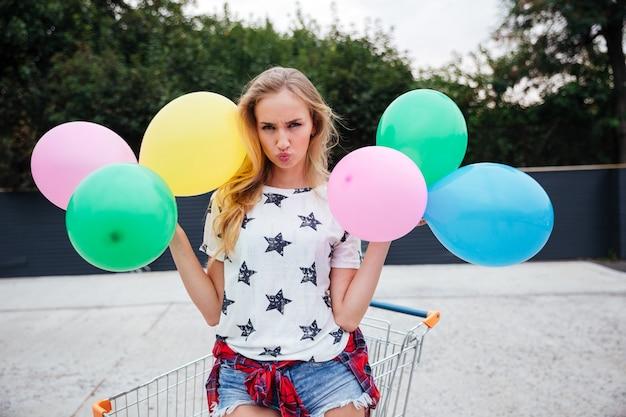 Bella donna bionda con palloncini colorati in città