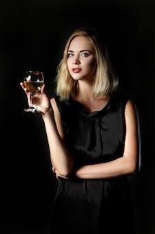 Bella donna bionda con un bicchiere di vino bianco su sfondo nero