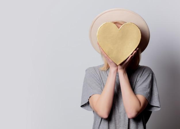 Bella donna bionda con scatola a forma di cuore sul muro bianco