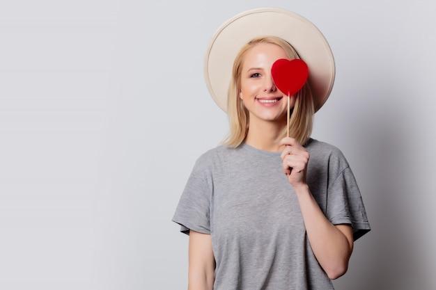 Bella donna bionda con la caramella di forma del cuore sulla parete bianca