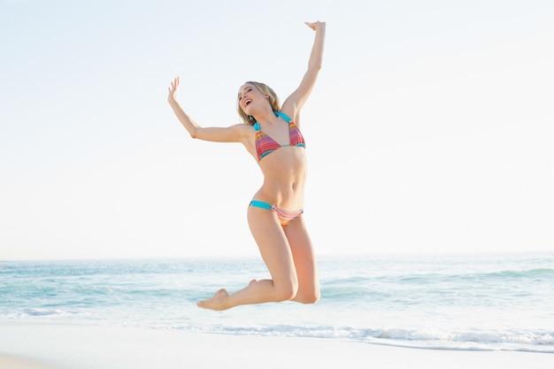 Bella giovane donna bionda che salta sulla spiaggia