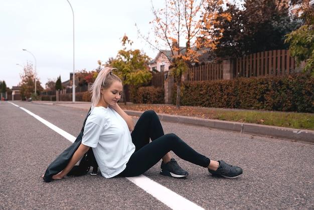 Bella giovane donna bionda sulla strada.
