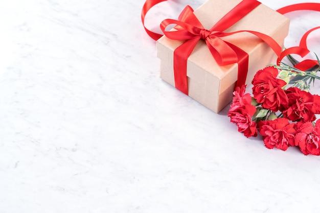 Bellissimi garofani in fiore con fiocco in nastro rosso isolato sulla moderna scrivania in marmo, vicino, copia dello spazio