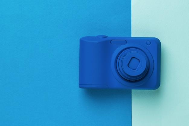 Bella fotocamera blu su sfondo bicolore. attrezzatura elegante per riprese di foto e video.