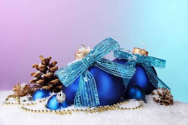 Bellissime palle e coni di natale blu sulla neve su sfondo luminoso