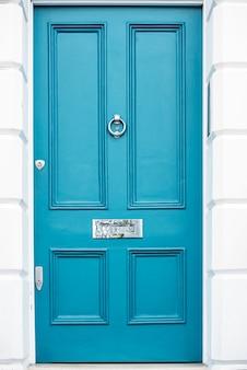 Bella porta blu con letterbox in una facciata della casa bianca a notting hill