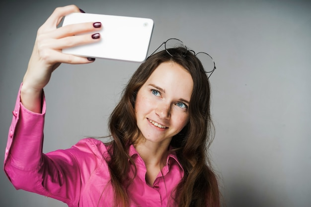La bella giovane donna dagli occhi azzurri in una camicia rosa sorride e fa il selfie