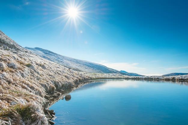 Bellissimo lago blu in montagna, ora dell'alba mattutina. paesaggio con sole splendente di neve