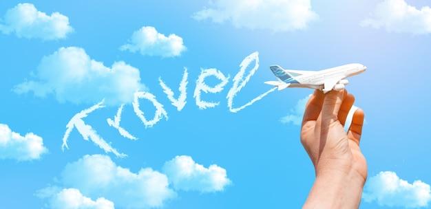 Bel cielo azzurro con nuvole e mano che tiene un aereo giocattolo e fumo con iscrizione travel