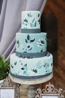Bella torta blu a tre livelli decorata con fiori su un supporto, sulla tavola di nozze.
