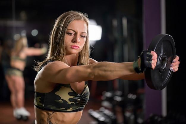 Donna bella culturista con manubri di sollevamento. ragazza sportiva che mostra il suo corpo ben addestrato. muscoli ben sviluppati con l'allenamento della forza.