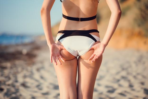 Bella ragazza in stile bohémien e abbronzata sulla spiaggia al sole