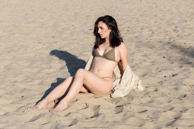 Bella ragazza abbronzata e in stile bohémien in spiaggia