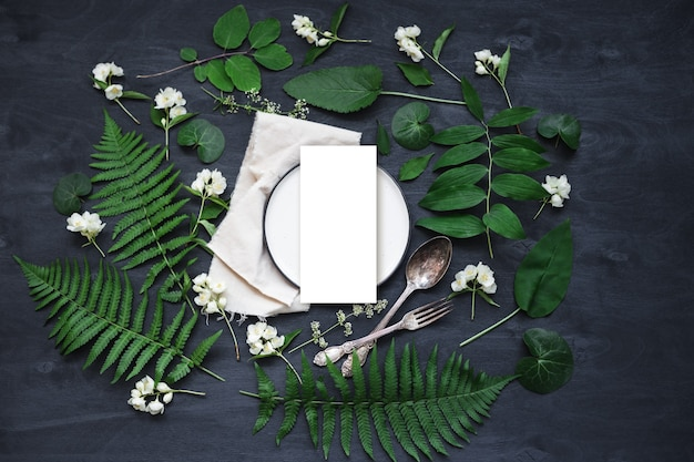 Bellissimo tavolo primaverile boho allestito mockup con decorazioni di fiori e piante selvatiche. foto vista dall'alto piatta alla moda.